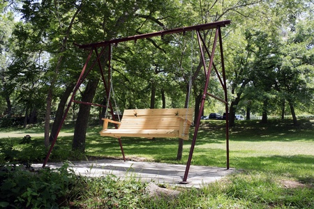 An empty wooden swing out in a garden Stock Photo - 13517047