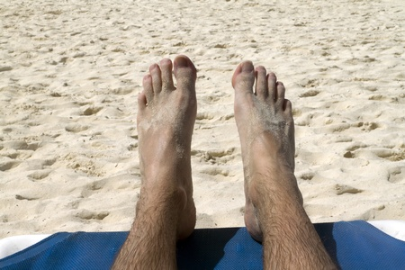 Two feet relaxing on a beach by the ocean photo