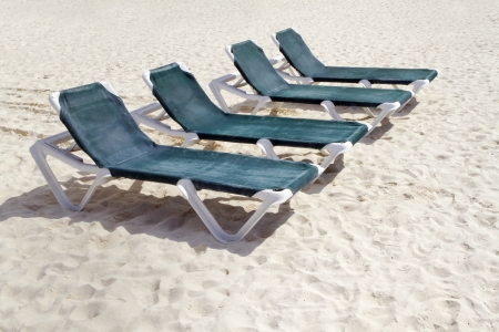 Rows of several green lounge chairs on the beach photo