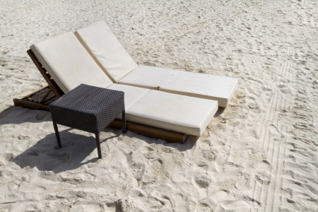 A pair of beach lounge chairs with table