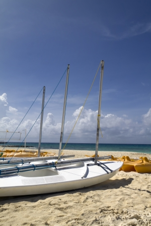 A personal sail boat on the beach by the ocean