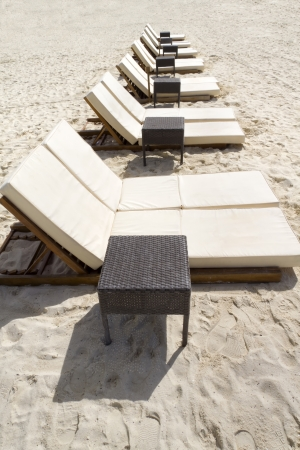 Rows of several lounge chairs on the beach