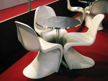 An aluminium circular table and three white plastic chairs on red moquette. Outdoor furniture mainly used in restaurants and cafe.