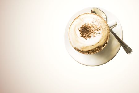 cappuccio: A cup of cappuccino with cocoa powder on the top. Tipical italian breakfast. Room for text. With clipping path.