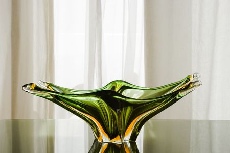 Precious green Murano glass plate on a green glass table. Soft light behind the white courtain on the back. Vibrant, bright reflections. photo