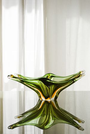 Precious green Murano glass plate on a green glass table. Soft light behind the white courtain on the back. Vibrant, bright reflections. Stock Photo