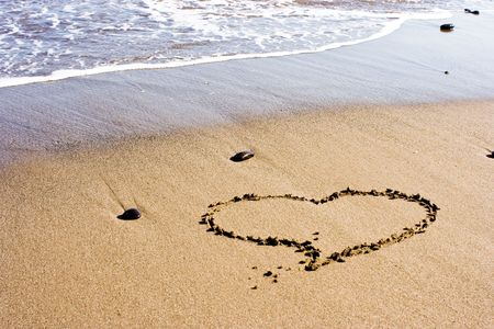 heart drawn in the sand next to the foamy wave