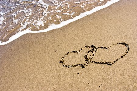 Two romantic hearts drawn in the sand next to the foamy wave