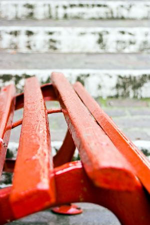 implication: Close up of a red wooden seat with, on the back, old white stairs made of stones. This can  be a concept image with the implication of a choise. Choise between stay and go. Useful also  for relax and rest concept. Relax before start to go. Or relax at the Stock Photo