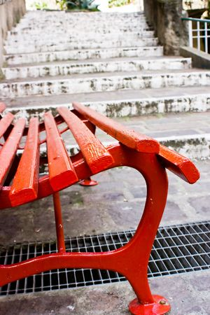 Close up of a red wooden seat with, on the back, old white stairs made of stones. This can  be a concept image with the implication of a choise. Choise between stay and go. Useful also  for relax and rest concept. Relax before start to go. Or relax at the Stock Photo