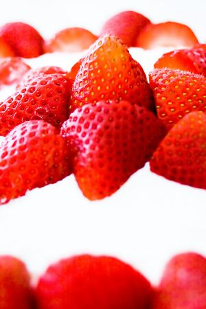 Closeup of strawberries and whipped cream topping of a delicious cake.
