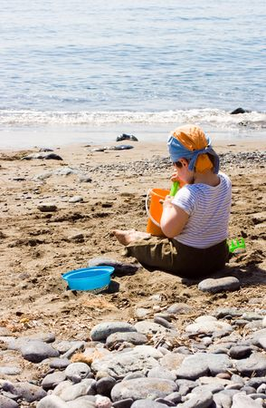 Two years child boy on the beach is playing with the sand. Stock Photo