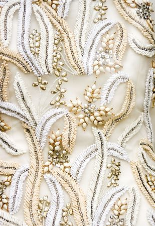 Closeup of the fabric of an antique wedding dress with precious decorations and embroidery. Perfect use as background or texture.