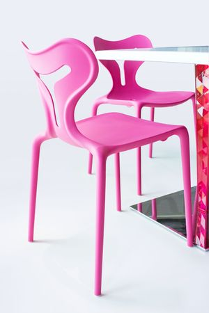 Two pink chairs with a table isolated on white. With clipping path.