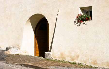 Rural arched door and a window with a vase of red geraniums flowers. Photo taken in a mountain village in Trentino, Val di Non, Alps, Italy. Space for copy.