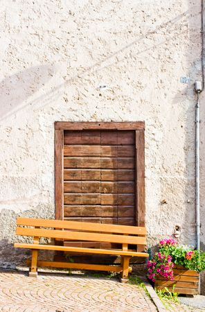 Rural door and bench with vases of red geraniums and pink petunia flowers. Photo taken in a mountain village in Trentino, Val di Non, Alps, Italy. Space for copy. photo