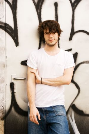 Attractive young man standing in front of a black and white graffiti wall and looking at the camera. 20-25 years old. A handle of a door is visible next to him. Useful for solitude, escape, relaxing, waiting concepts relating to urban youth culture.