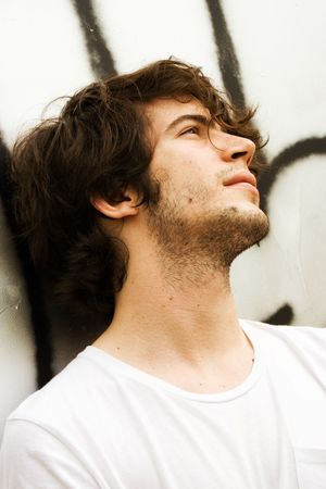 Close up of the face of an attractive young man watching up.  expression. Looking ahead, dreaming, contemplating concept. 20-25 years old. White graffiti background. Stock Photo