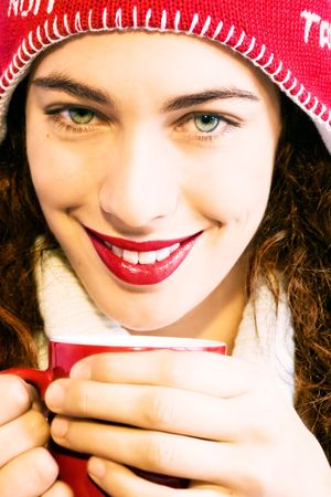 Pretty smiling girl  in winter clothes with a red cup of hot drink. Could be coffee, cappuccino, chocolate, tea. Warm and winter concept.