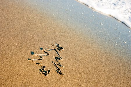 seasonal greetings: Christmas tree drawn in the sand on the shoreline. Holiday vacation concept.