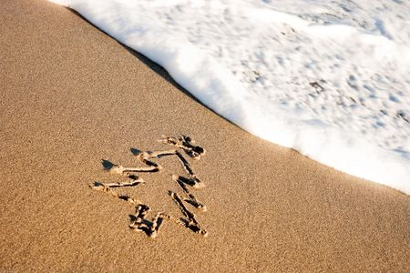 Christmas tree drawn in the sand on the shoreline. Winter Holiday vacation concept. Stock Photo