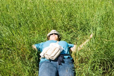 Woman in casual clothes is sleeping in a meadow. Leisure, relaxation, serenity concept. Space for copy.