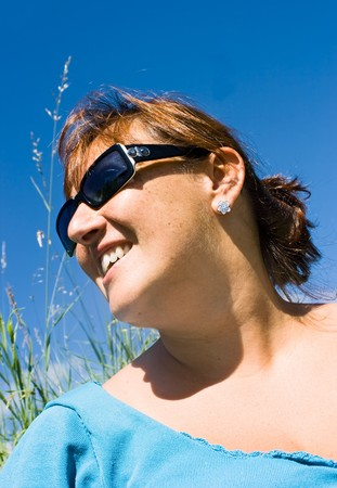 Happy smiley woman with sunglasses in a meadow, against blue clear sky. Happiness, serenity concept.