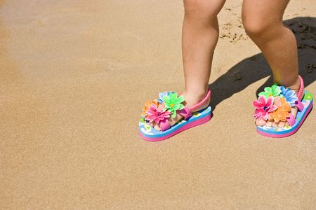 Legs of a two years old child girl on the sand, wearing a pair of a lovely flower decorated flip flops. Beach, summer, fun, vacation concept. Space for copy. Jpeg with path included. photo
