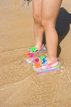 flip flops on the beach: Legs of a two years old child gir on the sand, wearing a pair of a lovely flower decorated flip flops. Beach, summer, fun, vacation concept. Space for copy.
