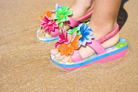Feet of a two years old child girl on the sand, wearing a pair of a lovely flower decorated flip flops. Beach, summer, fun, vacation concept. Space for copy. photo