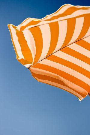Orange beach umbrella over blue sky background.  Stock Photo