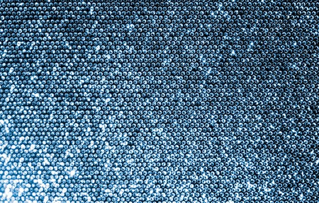 Silver fabric made of a grid of sparkling sequins. photo