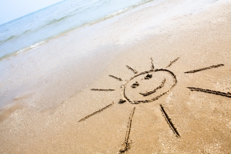 happy emoticon: Smiley sun drawing on the sand beach. Perfect for greeting cards, positive and happiness concept.