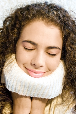 Beautiful young woman with a warm white sweater  Smiling and expressing satisfaction and positivity
