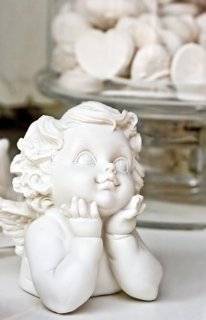 Statue of a white child angel, with candies in shape of heart in the back ground  Love concept  Useful for celebrations like wedding, anniversary, baptism   Stock Photo