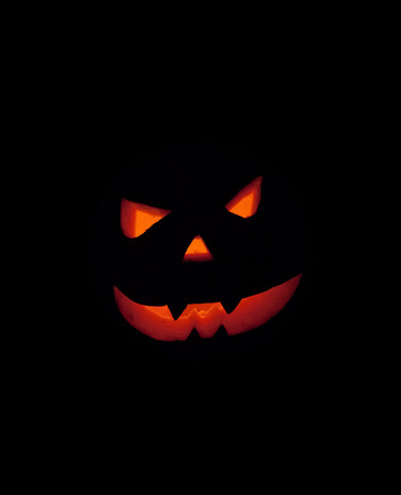 Scary smiling halloween face carved in a pumpkin. Isolated on black background. Clipping path in the jpeg file. Stock Photo