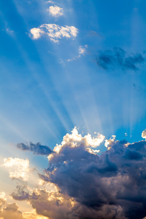 Sun rays behind the clouds in the blue sky. Religion and spirituality concept too.