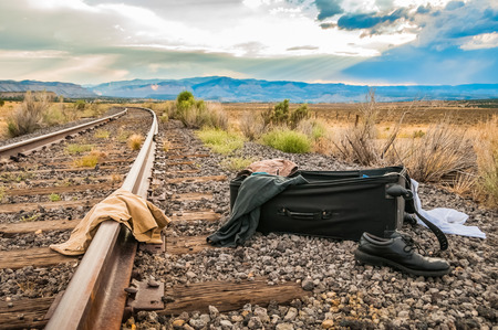 An open suitcase by the railroad tracks Imagens