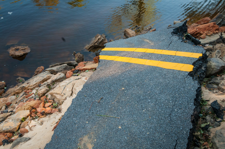 A broken road with water from a hurricane