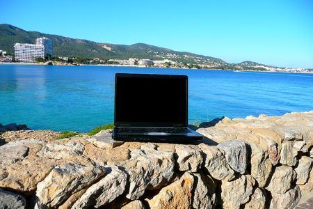 Laptop by the sea with blank screen for text photo