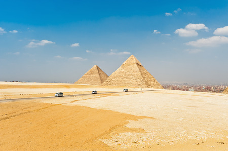 Pyramids with driving car in Egypt photo