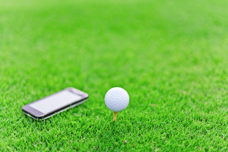 White golf ball on tee with a mobile Imagens