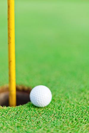 White golf ball on putting green Imagens