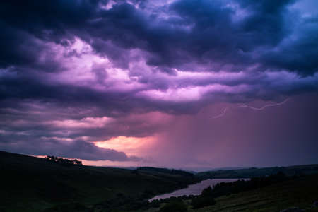 The colors of the storm with thunderbolts on night sky in Brecon Beacons National Park in Wales. Фото со стока