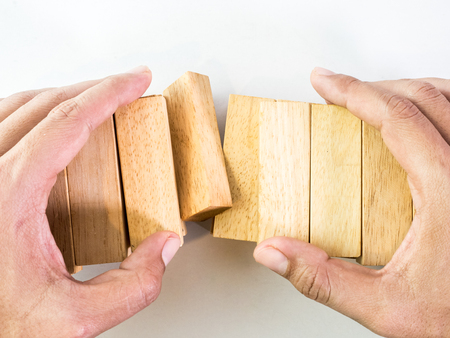 establishes: The hand establishes a wooden cube in row. on a white background
