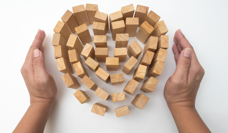 letterpress words: wooden block heart and hand hold concept protection your love on white background
