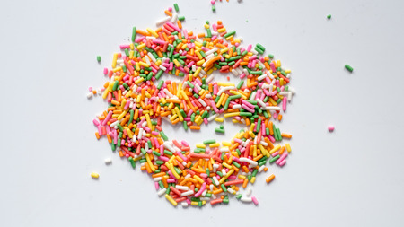 macro of rainbow sprinkles concept smile white background