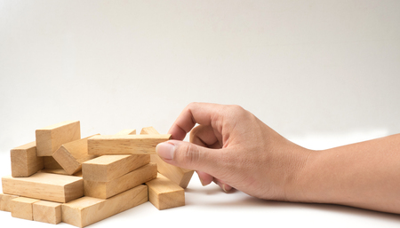 Wooden Blocks disrupted hand hold close up on white background