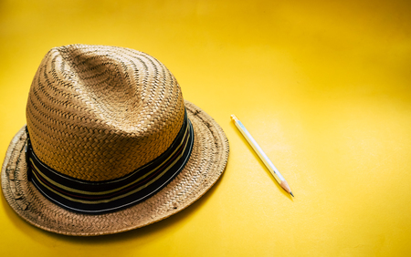 Hat wicker and pencil on yellow background color style vintage