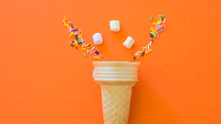 Ice cream base on orange background with colored Rainbow and marshmallow Sprinkles creative concept. Stock Photo